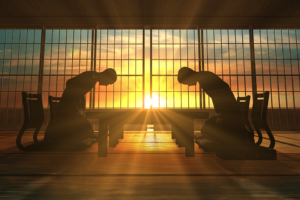 Two silhouettes bowing to each other in front of a sunset in a Japanese environment
