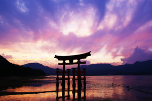Traditional Japanese gate with a beautiful lake and sunset in the background highlighting Japanese history and geography